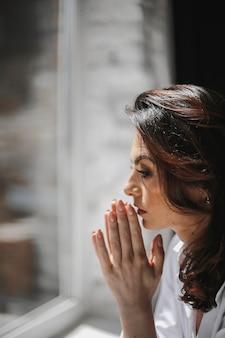 Portrait of beautiful caucasian woman praying near window on sunny day.