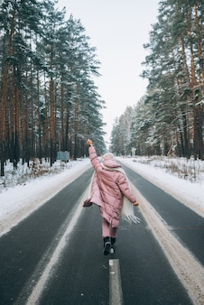 Portrait of a beautiful caucasian woman on a road in snowy forest