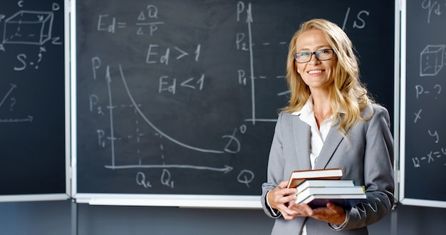 Portrait of beautiful caucasian woman teacher standing in classroom at board, smiling to camera and holding textbooks. female lecturer with books at blackboard with math formulas and drawings.