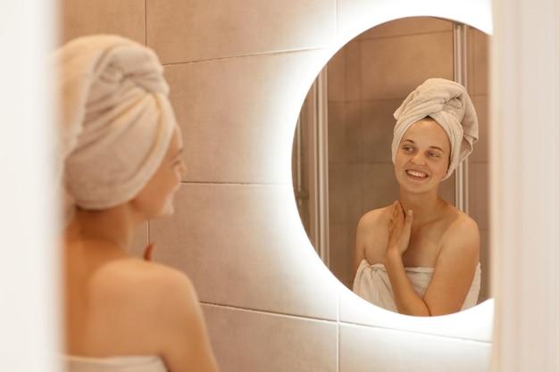Ritratto di bella donna caucasica con un asciugamano sui capelli che si tocca il collo in bagno, guardando il suo riflesso nello specchio, in posa dopo aver fatto la doccia.