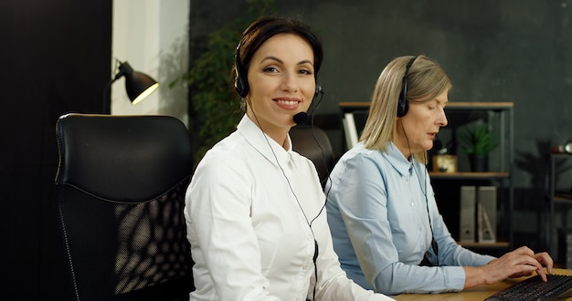 Portrait of beautiful caucasian young woman in headset working at computer in call center.