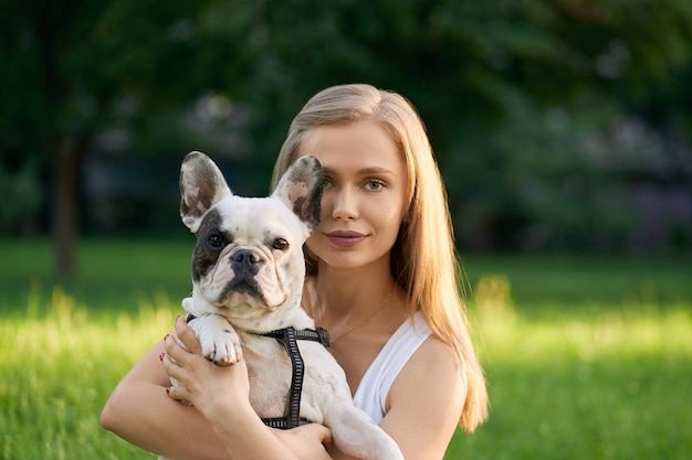 Portrait of beautiful caucasian young woman holding adult french bulldog and looking directly in summer park.