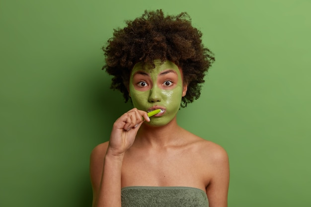 Portrait of beautiful charming afro american lady has morning routine procedures, wears facial anti aging mask for rejuvenation, brushes teeth, wrapped in bath towel, isolated over green wall.