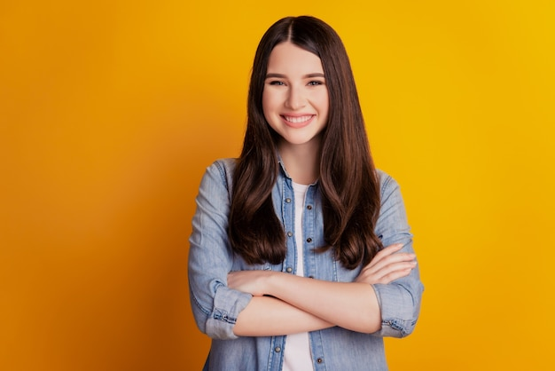 Portrait of beautiful charming positive girl crossed hands isolated over yellow background