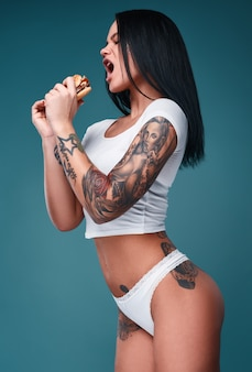 Portrait of beautiful charming woman with tattoos holding a hamburger