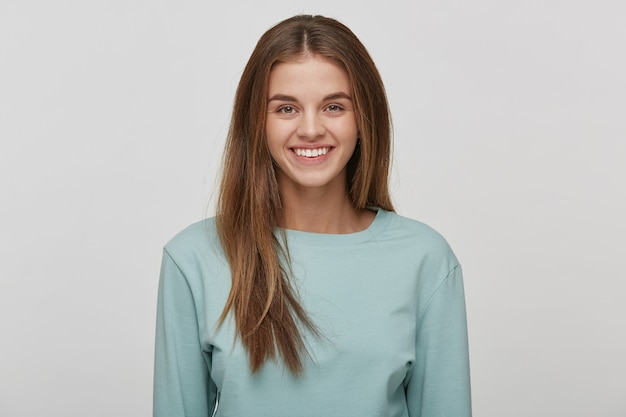 Portrait of a beautiful cheerful happy young woman with natural make-up and well-groomed hair, smiles