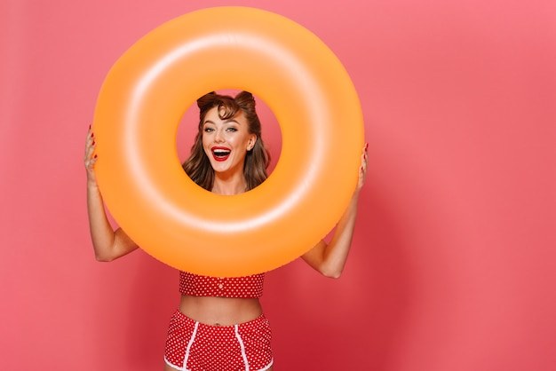 Portrait of a beautiful cheerful pin-up woman wearing swimsuit standing isolated, holding inflatable rubber ring