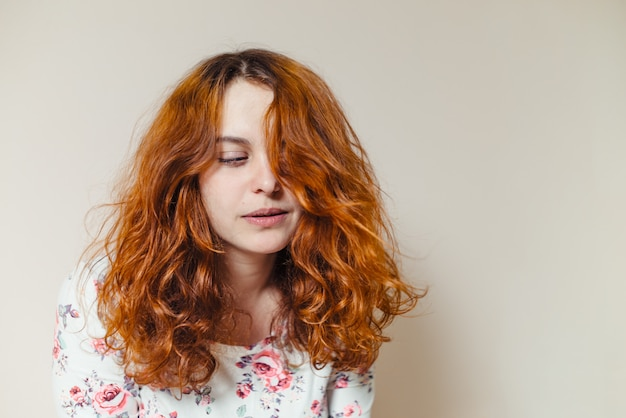 Portrait of beautiful cheerful redhead girl with curly hair over beige scene