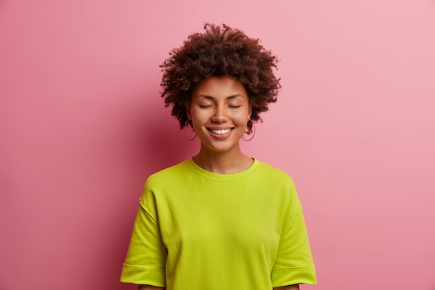 Portrait of beautiful cheerful woman closes eyes and smiles with pleasure, wears casual green t shirt, hears pleasant words of support, isolated in pink wall. happy emotions and feelings