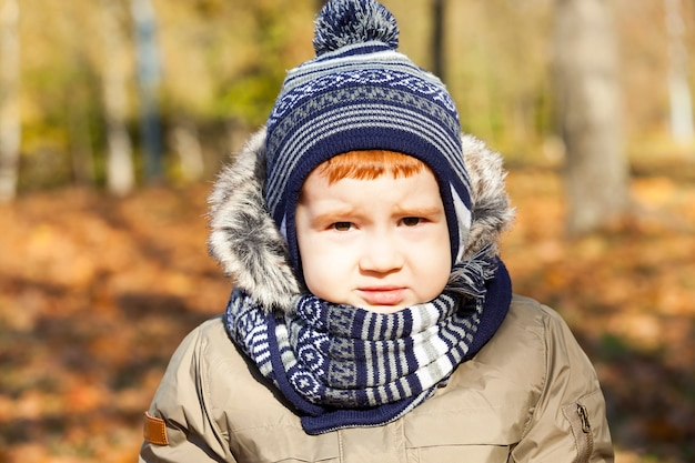 Portrait of a beautiful child with a upset expression on his face , the boy is dressed in warm clothes, autumn season , photo closeup ,