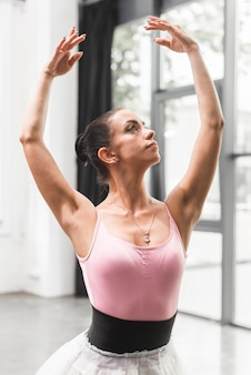 Portrait of beautiful classical ballerina with her arm raised