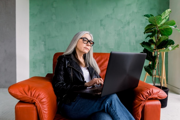 Portrait of beautiful concentrated senior 60-aged lady with long gray hair, wearing trendy modern clothes and eyeglasses, sitting in red armchair and working on laptop
