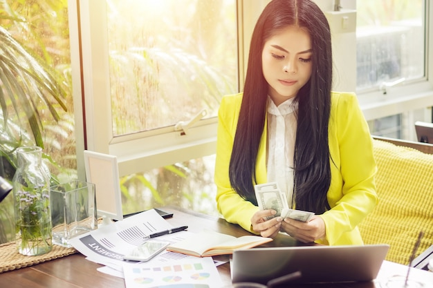 Portrait of beautiful and confident asian business woman in working with notebook laptop and book manage job work at workplace.