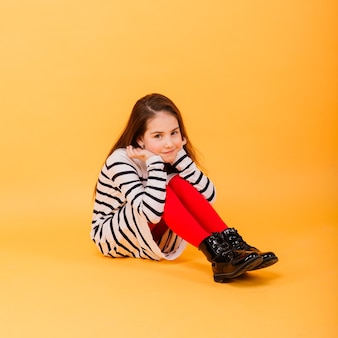 Portrait of a beautiful and confident girl showing emotions and thumbs up isolated on yellow