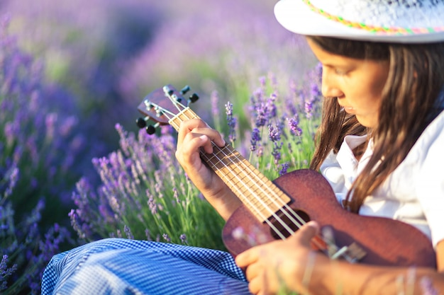 Portrait of a beautiful country girl with brown hair who learns to play on the ukulele in a beautiful place among lavender flower