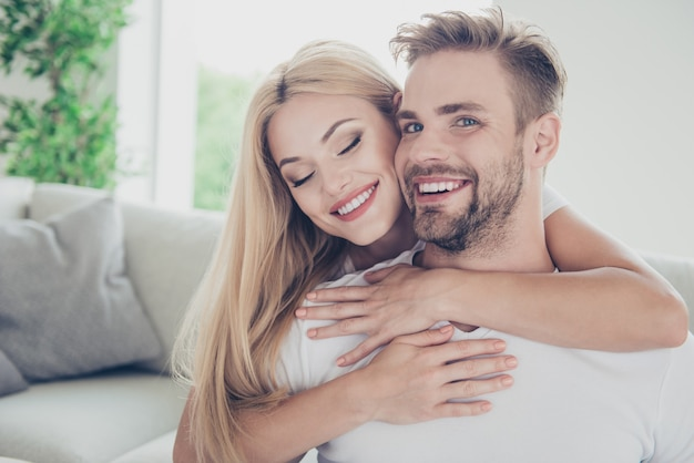 Portrait of beautiful couple in casual tshirts at home piggyback