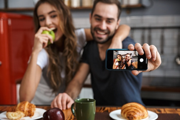 Portrait of beautiful couple man and woman taking selfie photo on cell phone while having breakfast in kitchen at home