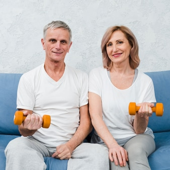 Portrait of a beautiful couple sitting on sofa holding dumbbells