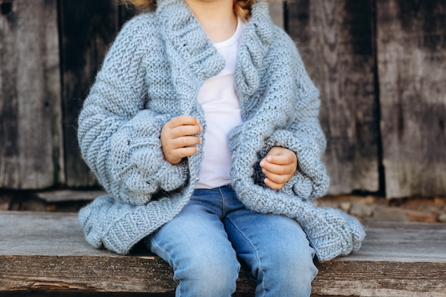 Portrait of a beautiful curly girl in a blue knitted sweater near a wooden wall