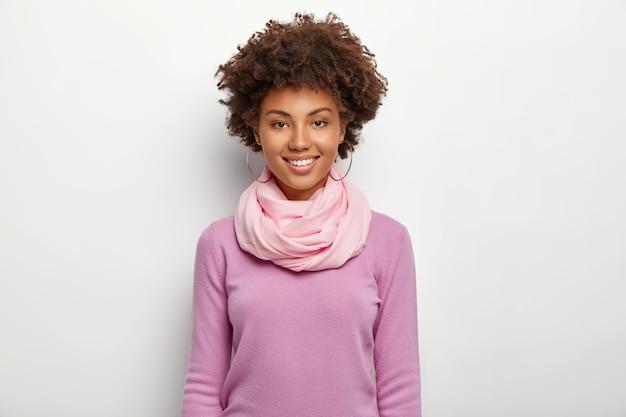 美丽的卷发妇女画像穿着紫色紫罗兰色套头衫和丝绸围巾,直接看,表达良好的情感,模特对白色墙。人,种族,时尚