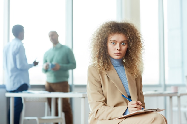 Portrait of beautiful curly haired woman while posing in business office, copy space