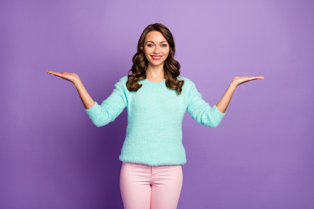 Portrait of beautiful curly lady holding open arms advising black friday low shopping prices novelty products wear casual teal fluffy pullover pink pastel pants.