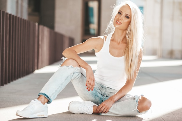Portrait of beautiful cute blond girl in white t-shirt and jeans posing outdoors. cute girl sitting on asphalt on the street