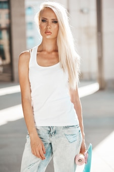 Portrait of beautiful cute blond girl in white t-shirt and jeans posing outdoors. girl with blue penny skateboard  on the street
