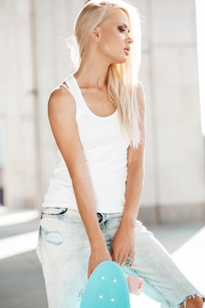 Portrait of beautiful cute blond girl in white t-shirt and jeans posing outdoors