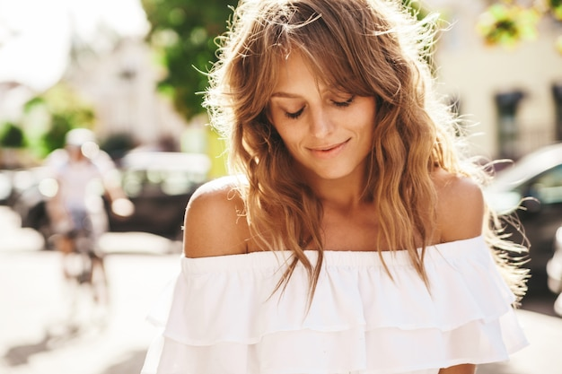 Portrait of beautiful cute blond teenager model with no makeup in summer hipster white dress clothes posing on the street background. closed eyes