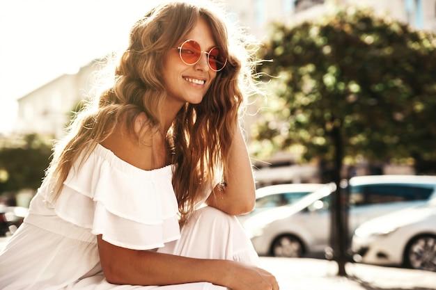 Il ritratto di bello modello biondo sveglio dell'adolescente senza trucco in vestito bianco dai pantaloni a vita bassa dell'estate copre la seduta sui precedenti della via