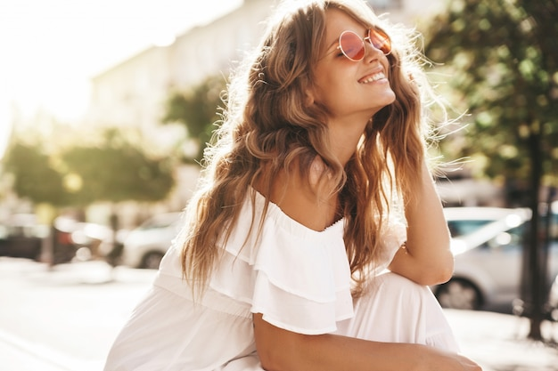 Portrait of beautiful cute blond teenager model with no makeup in summer hipster white dress clothes sitting on the street background
