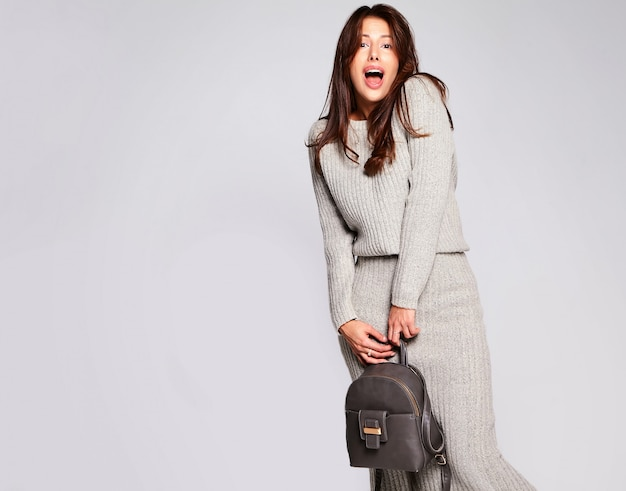 Portrait of beautiful cute brunette woman model in casual autumn gray sweater clothes with no makeup isolated on gray with handbag