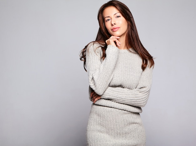 Portrait of beautiful cute brunette woman model in casual autumn gray sweater clothes with no makeup isolated on gray