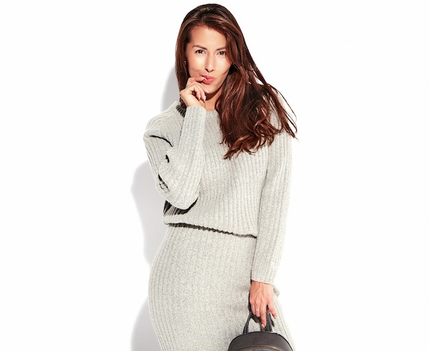Portrait of beautiful cute brunette woman model in casual autumn gray sweater clothes with no makeup isolated on white with handbag