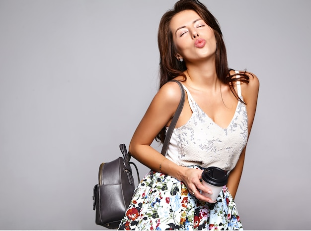 Portrait beautiful cute brunette woman model in casual summer clothes with no makeup isolated on gray. giving air kiss and drinking fresh coffee