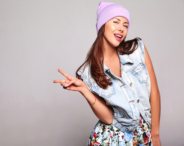 Portrait of beautiful cute brunette woman model in casual summer jeans clothes with no makeup in purple beanie isolated on gray. showing peace sign