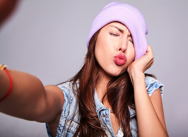 Portrait of beautiful cute brunette woman model in casual summer jeans clothes with no makeup in purple beanie making selfie photo on phone isolated on gray. giving air kiss