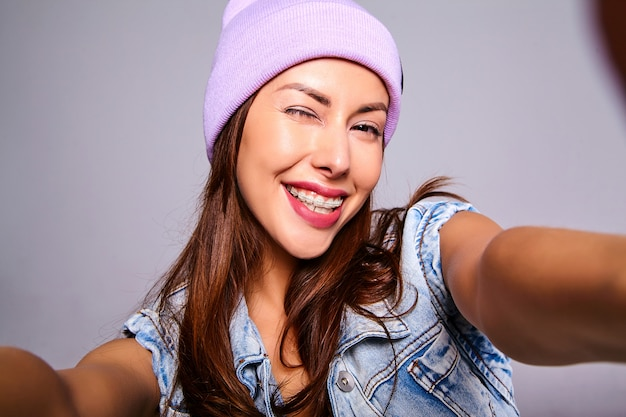 Portrait of beautiful cute brunette woman model in casual summer jeans clothes with no makeup in purple beanie making selfie photo on phone isolated on gray