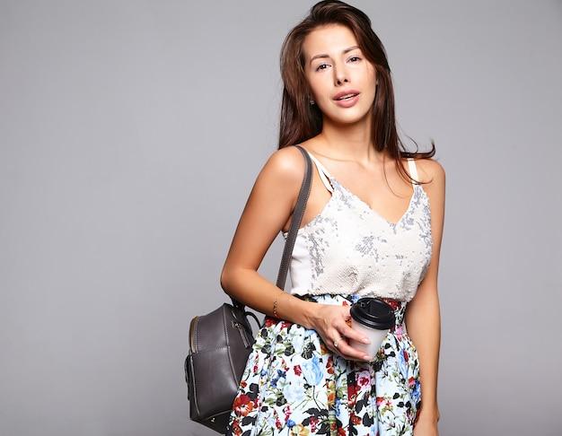 Модель женщины брюнет портрета красивая милая в вскользь одеждах лета без состава изолированного на сером цвете. пить свежий кофе