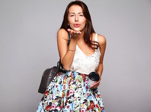 Модель женщины брюнет портрета красивая милая в вскользь одеждах лета без состава изолированного на сером цвете. поцелуй в воздухе и пить свежий кофе