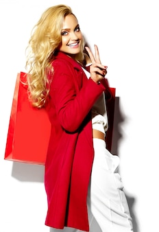 Portrait of beautiful cute happy sweet smiling blonde woman girl holding in her hands big shopping bag in hipster red clothes isolated on white