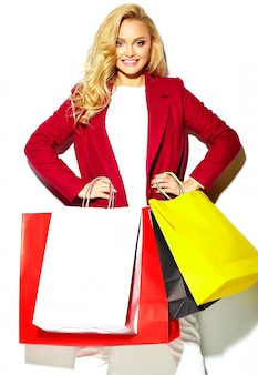 Portrait of beautiful cute happy sweet smiling blonde woman girl holding in her hands big shopping colorful bags in red jacket hipster isolated on white