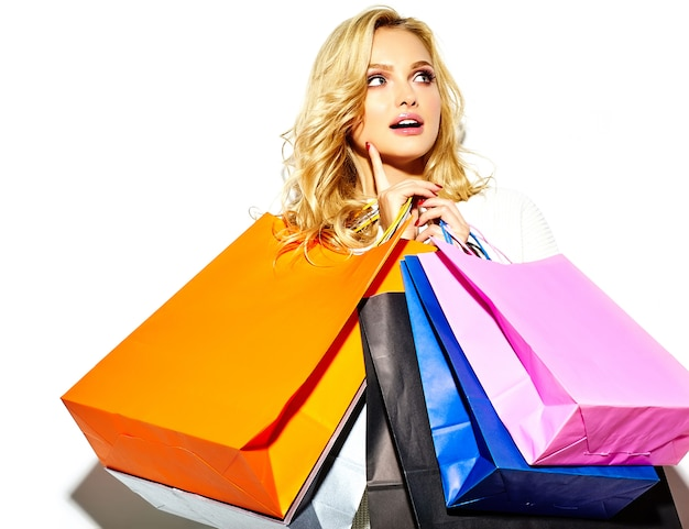Portrait of beautiful cute happy sweet smiling blonde woman woman holding in her hands big shopping colorful bags in  hipster clothes isolated on white