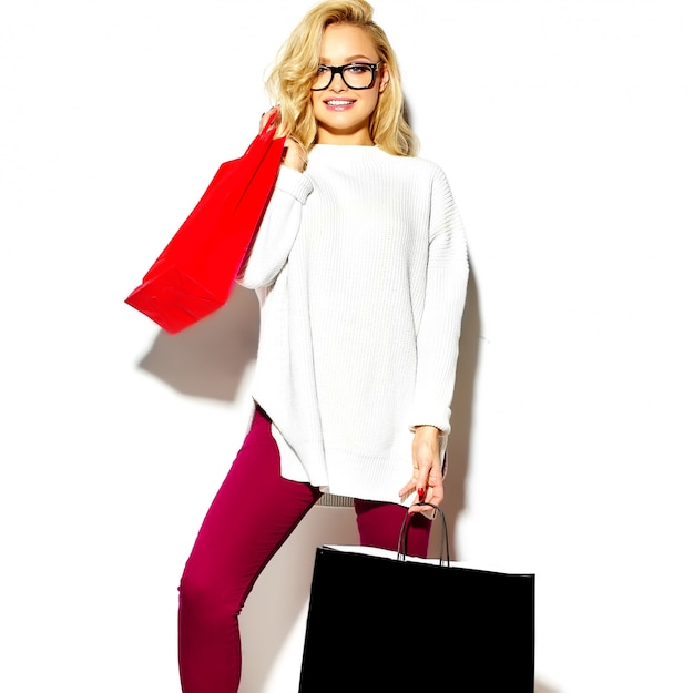 Portrait of beautiful cute happy sweet smiling blonde woman woman holding in her hands big shopping colorful bags in red jacket hipster isolated on white