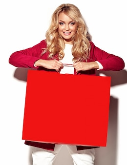 Portrait of beautiful cute happy sweet surprised blonde woman girl holding in her hands big shopping bag in hipster red clothes isolated on white