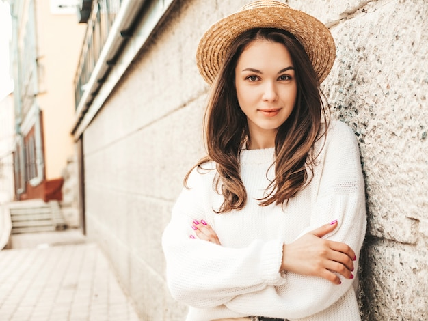 Portrait of beautiful cute model. female dressed in warm hipster white sweater and hat. trendy girl posing near wall in the street. funny and positive woman hugging herself