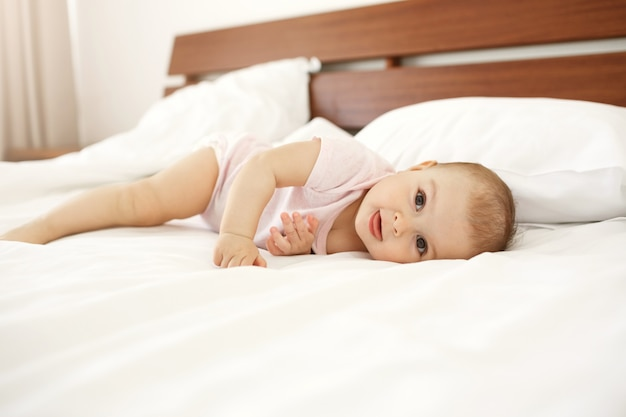 Portrait of beautiful cute newborn baby showing tongue lying on bed at home.