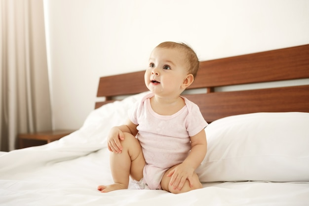 Portrait of beautiful cute nice newborn baby in pink shirt sitting on bed at home.