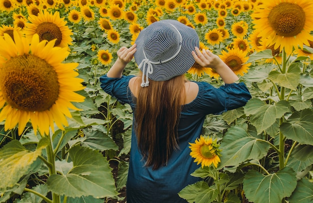Portrait of a beautiful, cute, sexy girl in a blue dress with flowers of a sunflower. emotion of pleasure, freedom concept, lifestyle. stands with his back to his hat.